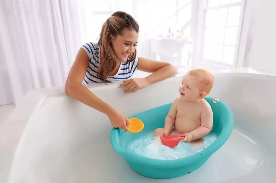 Переливание воды в ванной при купании ребенка